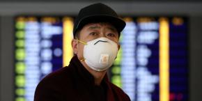 coronavirus-covid-19-un-passager-porte-un-masque-tandis-qu-il-marche-dans-l-aeroport-international-de-hong-kong-le-7-fevrier-2020