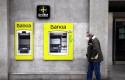 ep archivo - un hombre con mascarilla pasa por delante de un cajero de bankia