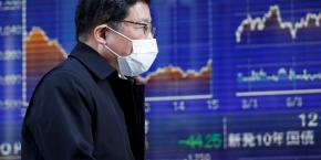 bourse-un-homme-portant-un-masque-passe-devant-un-tableau-electronique-montrant-des-graphiques-de-recents-mouvements-de-l-indice-nikkei